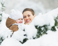 Portrait of smiling mother and baby in winter park Stock Photo