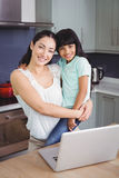 Portrait of smiling mother carrying daughter with laptop Royalty Free Stock Images