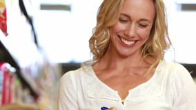 Smiling mother checking grocery list. Portrait of smiling mother checking grocery list in grocery store stock footage