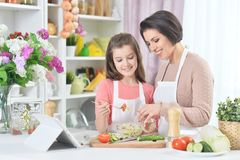 Smiling mother and daughter cooking together at kitchen Royalty Free Stock Photography