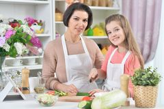 Portrait of smiling mother and daughter cooking together at kitchen royalty free stock images