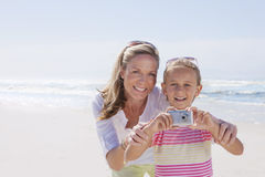 Portrait of smiling mother and daughter with digital camera on sunny beach stock photo