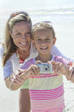 Portrait of smiling mother and daughter with digital camera on sunny beach royalty free stock images