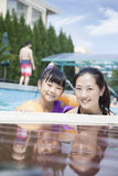 Portrait of smiling mother and daughter in the pool by the edge looking at camera Stock Photography