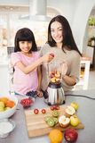 Portrait of Smiling mother and daughter preparing fruit juice Royalty Free Stock Photos