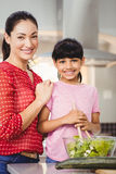 Portrait of smiling mother and daughter preparing salad Stock Images