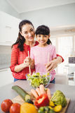 Portrait of smiling mother and daughter preparing vegetable salad Royalty Free Stock Photos