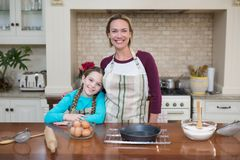 Smiling mother and daughter standing in the kitchen Royalty Free Stock Image