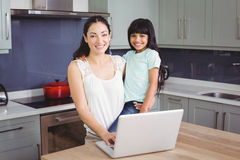 Portrait of smiling mother and daughter using laptop Royalty Free Stock Photo