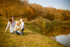 Portrait of smiling mother and daughters on autumn lake Royalty Free Stock Photography