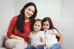 Portrait of smiling mother and daughters at home Stock Photography