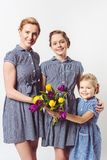 Portrait of smiling mother and daughters in similar dresses with bouquet of tulips. On grey royalty free stock photo