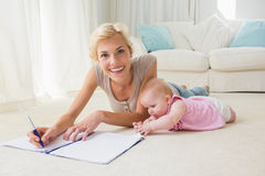 Portrait smiling mother with her baby girl writting on a copybook Stock Images