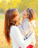 Portrait smiling mother hugging child in warm sunny autumn Stock Photography