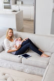 Portrait of smiling mother sitting with her baby in living room Royalty Free Stock Images