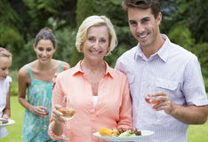 Portrait of smiling mother and son with barbecue and wine Royalty Free Stock Images