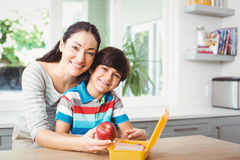 Portrait of smiling mother and son with lunch box Stock Image