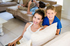 Portrait of smiling mother and son sitting on sofa Stock Image