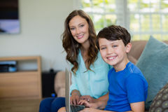Portrait of smiling mother and son sitting on sofa using laptop. In living room at home Royalty Free Stock Image