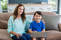 Portrait of smiling mother and son sitting on sofa using laptop. In living room at home Stock Images
