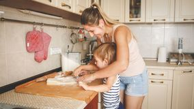 Portrait of young smiling mother teaching her 3 years old toddler boy baking and making cookies on kitchen. Portrait of smiling mother teaching her 3 years old royalty free stock photo