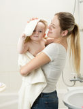Portrait of smiling mother wiping her baby with towel after havi Stock Photography