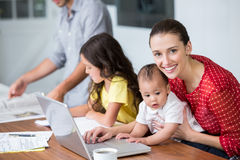 Portrait of smiling mother working on laptop with baby Stock Images