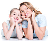 Portrait of smiling mother and young daughter. Portrait of happy white mother and young daughter lying on the floor- isolated. Happy family people concept stock images