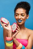 Portrait of smiling mulatto woman with bright cosmetics on face. Tasting ripe pitahaya cut in half isolated in studio over blue background Royalty Free Stock Photos