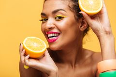 Portrait of smiling mulatto woman with colorful makeup tasting j. Uicy ripe orange holding parts in both hands near face isolated over yellow wall Stock Image