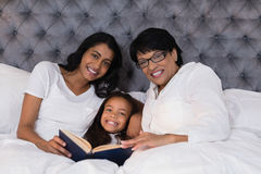 Portrait of smiling multi-generation family with book resting on bed Stock Image