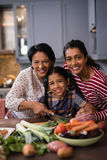 Portrait of smiling multi-generation family preparing food in kitchen Royalty Free Stock Images