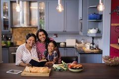 Portrait of smiling multi-generation family sitting in kitchen. Portrait of smiling multi-generation family sitting together in kitchen at home stock photos