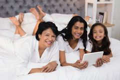 Portrait of smiling multi-generation family using digital tablet while lying on bed Stock Image