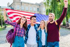 portrait of smiling multicultural students with american flag royalty free stock images