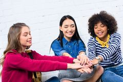 Portrait of smiling multicultural students holding. Hands together stock photo