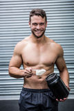 Portrait of smiling muscular man making protein cocktail Royalty Free Stock Image