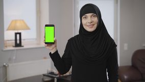 Portrait of smiling muslim woman in hijab holding smartphone with green screen. Modern eastern lady in black clothes