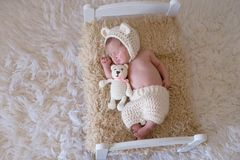 Newborn Baby Girl with Stuffed Bear. Portrait of a smiling newborn baby girl wearing a bear bonnet. She is cudling a stuffed bear and lying on a tiny bed royalty free stock photography