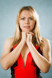 Portrait of smiling nice blonde woman. On a blue background Royalty Free Stock Images