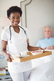 Portrait of smiling nurse with breakfast in tray while senior man lying on bed Stock Photography