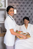 Portrait of smiling nurse giving breakfast to patient resting on bed Stock Photos