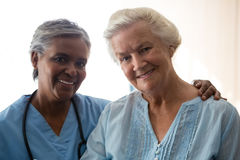 Portrait of smiling nurse and senior woman in nursing home. Portrait of smiling nurse and senior women standing in nursing home Royalty Free Stock Photography