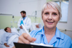 Portrait of smiling nurse writing on clipboard Royalty Free Stock Photos
