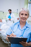 Portrait of smiling nurse writing on clipboard. In hospital room Royalty Free Stock Image