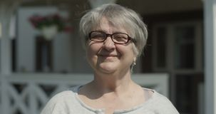 Portrait of Smiling Old Woman with Glasses Looking at the Camera Outdoors on Sunny Day at the Nursing Home shot on Red stock footage