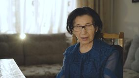 960e0f0303 Portrait of smiling old woman puts on glasses and looks at camera stock  video footage