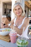 Smiling older woman eating salad at restaurant. Portrait of smiling older woman eating salad at restaurant Royalty Free Stock Images