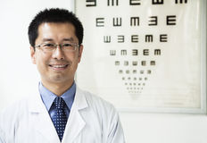 Portrait of smiling optometrist with an eye chart in the background Royalty Free Stock Photography