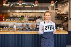 Portrait of smiling owner standing in his restaurant with open signboard. Young entrepreneur woman at small business family restaurant looking at camera, Chef royalty free stock photo